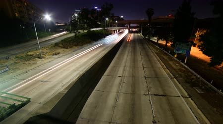 cauda : Time lapse footage with zoom in motion of light trails of cars on Interstate 110 Freeway in downtown Los Angeles at night Stock Footage