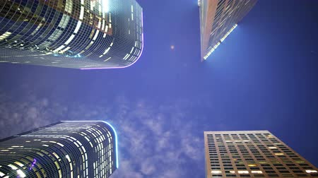 moderno : Time lapse footage with zoom out motion of low angle shot of skyscrapers with stars  clouds at night in downtown Los Angeles, California