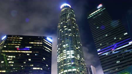 небоскреб : Time lapse footage with zoom in motion of low angle shot of skyscrapers with clouds at night in downtown Los Angeles, California