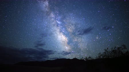 стрельба : 3 axis motion controlled astrophotography time lapse footage with dolly down, tilt down  pan right motion of Milky Way galaxy over desert landscape through dawn in Death Valley National Park, California