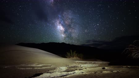дюна : Astrophotography time lapse footage with tilt up motion of Milky Way galaxy over desert sand dunes in Death Valley National Park, California Стоковые видеозаписи