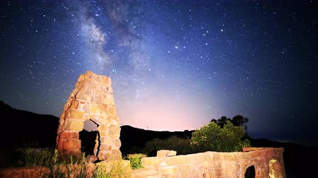 perili : Astrophotography time lapse footage with tilt up motion of milky way galaxy spanning over arch-shaped abandoned brick ruin structure at Knapps Castle in Santa Barbala, California
