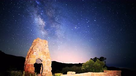 perili : Astrophotography time lapse footage with tilt down motion of milky way galaxy spanning over arch-shaped abandoned brick ruin structure at Knapps Castle in Santa Barbala, California Stok Video