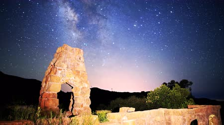 perili : Astrophotography time lapse footage with pan right motion of milky way galaxy spanning over arch-shaped abandoned brick ruin structure at Knapps Castle in Santa Barbala, California Stok Video