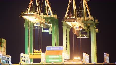 ithalat : Time lapse footage with zoom out motion of industrial cranes loading containers onto container ship at a shipyard in port of Los Angeles at night