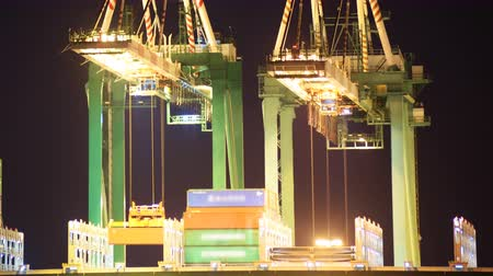 importação : Time lapse footage of industrial cranes loading containers onto container ship at a shipyard in port of Los Angeles at night -Long Shot- Vídeos