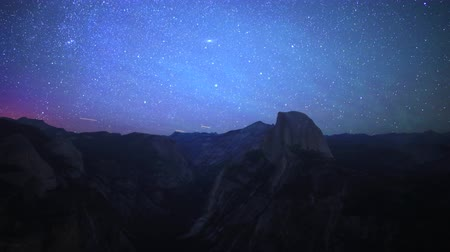 modrá obloha : Time lapse footage with tilt up motion of starry sky and low latitude aurora over Half Dome in Yosemite National Park, California