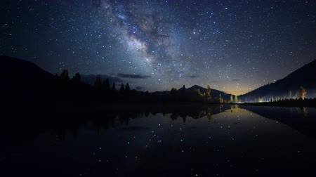 árvores : Astrophotography time lapse footage with pan right motion of milky way galaxy spanning over reflective alpine lake in Yosemite National Park, California