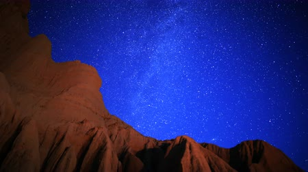 taş : Astrophotography time lapse footage of Milky Way galaxy rising over rugged sandstone formation at moon set in Mojave Desert at Red Rock Canyon State Park, California