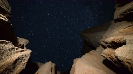 стрельба : Astrophotography time lapse footage with pan left motion of starry sky over eroded sandstone canyon walls at Red Rock Canyon State Park in Mojave Desert, California