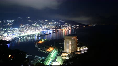 esquerda : Motion controlled tilt downpan left time lapse footage with zoom out motion of night cityscape in Atami, Japan
