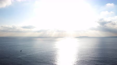 esquerda : Time lapse footage with pan left motion of morning sun ray through heavenly cloudscape over sea horizon