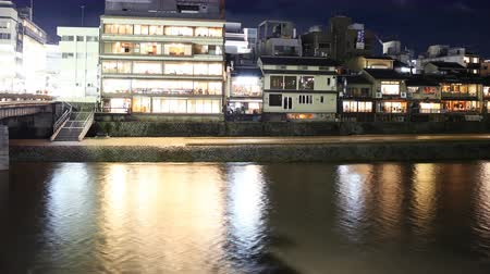 4K Motion controlled pan right time lapse footage with zoom inout motion of traditional restaurant district along Kamogawa river in Kyoto, Japan at night