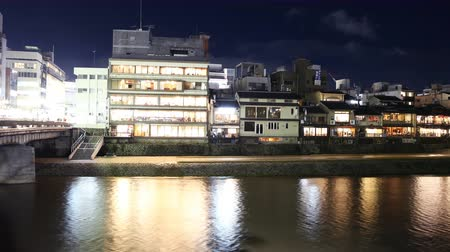 4K Motion controlled pan right time lapse footage with zoom in motion of traditional restaurant district along Kamogawa river in Kyoto, Japan at night