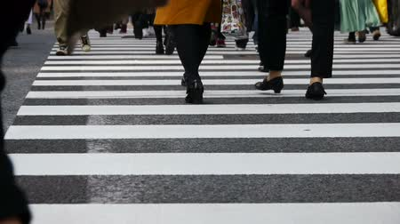 Footsteps of commuters in famous Shibuya crosswalk at rush hour in Tokyo, Japan