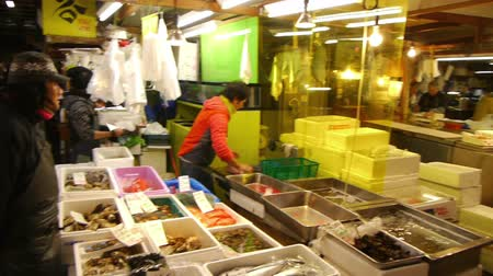 Footage of people shopping for fresh seafood product at Tsukiji Fish Market district in Tokyo, Japan -pan left-