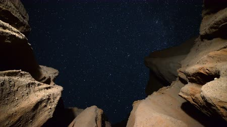 Astrophotography time lapse footage with zoom in motion of starry sky over eroded sandstone canyon walls at Red Rock Canyon State Park in Mojave Desert, California