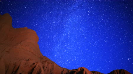 Astrophotography time lapse footage with zoom out motion of Milky Way galaxy rising over rugged sandstone formation at moon set in Mojave Desert at Red Rock Canyon State Park, California