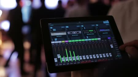 clubhouse : The DJ controls the music with the tablet and equalizer, Stock Footage