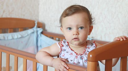 despreocupado : Beautiful baby girl standing in bed with serious look