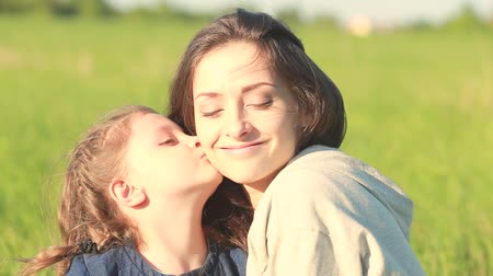 мама : Happy emotional daughter hugging and kissing with love her young smiling mother on summer background Стоковые видеозаписи