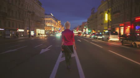 citynight : Night dark view of a road and back view of girl going at center of road when cars are moving, Nevsky prospect, Saint Peterburg, Russia