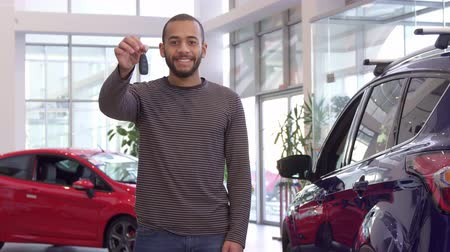 sprzedawca : Attractive bearded guy holding car key in his hand. Handsome african american man standing near new crossover at the showroom. Long shot of young male customer buying his vehicle