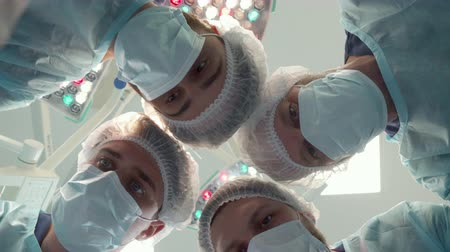cirurgião : Surgical team in medical masks bending over the patient. Close up of four male surgeons working with their patient. Camera shooting pov from patients position