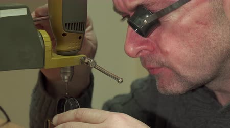 perforation : Middle aged watchmaker making perforation in some watch piece. Bald repairer fixing part on drill press. Close up of caucasian man raising up drill head