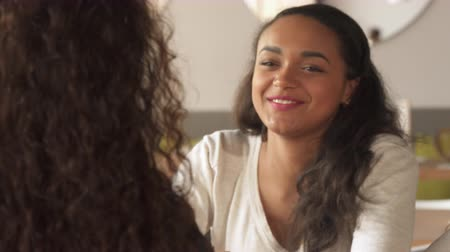 dialog : Pretty african american girl asking some question to her female friend at the cafe. Cute brown haired woman taking a cup of coffee from the table. Close up of attractive young lady folding her palms near her cheek