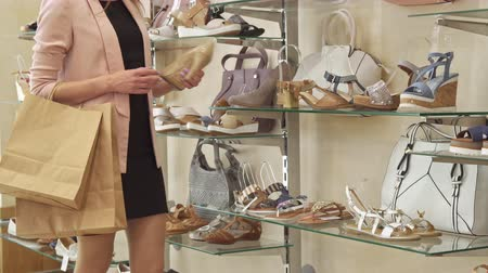 footgear : Young woman stopping near the beige shoes at the shop. Low shot of slender girl examining high heel pumps at the boutique. Leggy female buyer touching some stylish footwear at the rack