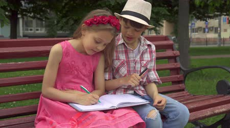 outside : Pretty little girl drawing on one page of notebook while her male friend on another. Attractive caucasian kids sitting on the bench in the park. Cute blond female child holding album on her laps