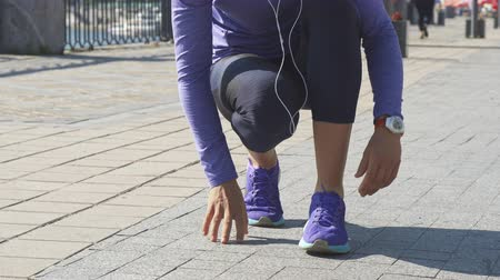 lower part : Young woman stops and crouches. She fix the strings on her sneakers. She changes legs, fixing shoes. Then girl straightens Stock Footage