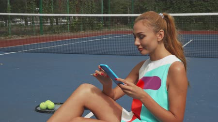 spotswear : Girl sitting on a tennis court and holding smartphone. She looks in front of her, then lowers her gaze to phone. Racket, balls ant tennis net are behind her Stock Footage