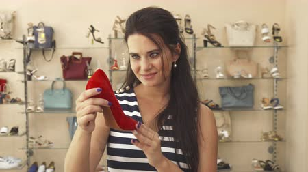 footgear : Brunette examining red shoe. Then she looks at camera and stretches shoe out to it. Woman in shoe shop