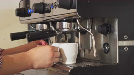 ristretto : The barista puts mugs in a special coffee machine. He is making two cups of coffee. He waits until the coffee is ready