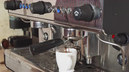 ristretto : The barista turns on the espresso machine.He clicks on the special button. After that he puts the cup in the machine. The barista is waiting until the coffee is ready Stock Footage