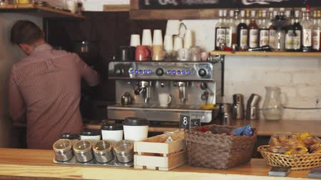 ristretto : The barista is standing at the bar. He is making coffee. On the bar counter lie various spices and desserts. The barista works in the cafe Stock Footage