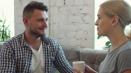 parecer : The man and woman are sitting at the sofa in the cafe. The are drinking coffee. They have nice conversation. They seem relaxed and happy