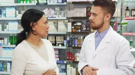 consist : A woman is standing in a drugstore and tells the pharmacist something. He listens to her attentively. Then he gives it to her with her purchases. They look at the camera and smile Stock Footage