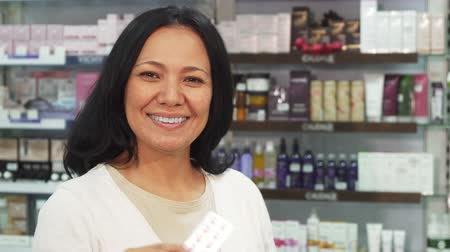 consist : The woman looks healthy and satisfied. She holds a packet of pills in her hands. Then she shows a thumbs up. A woman is standing in the middle of a pharmacy
