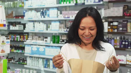consist : A woman is holding a bag with her purchases. She looks into it and looks very surprised. Then she laughs and smiles at the camera. A woman is standing in the middle of a pharmacy