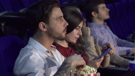 tmavé vlasy : Four friends are sitting in the cinema hall and watching the movie