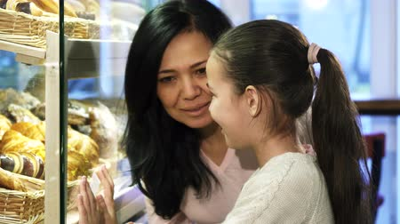 азиатский : Mother and daughter shopping at the bakery choosing pastry in the showcase Стоковые видеозаписи