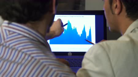 sucessful : Rearview close up of two businessmen discussing diagram on the laptop screen Stock Footage