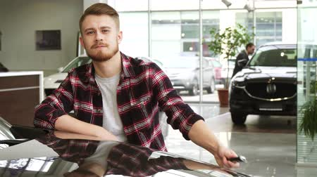 automobilový průmysl : Young handsome man showing car keys to his new auto at the dealership salon