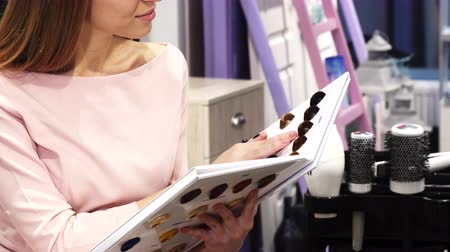 broszura : Cropped shot of a woman choosing hair dye color from the chart at the hairdresser salon