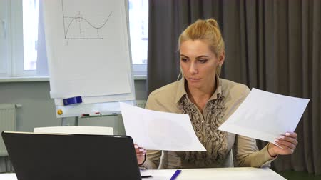 puzzled : Mature business woman looking confused while examining documents