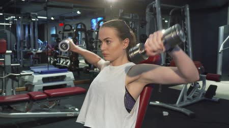 cabeça e ombros : Athletic girl is pumping muscles of her arms