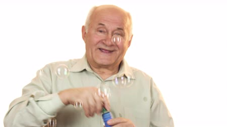 positive ageing : Senior cheerful man blowing bubbles isolated on white Stock Footage
